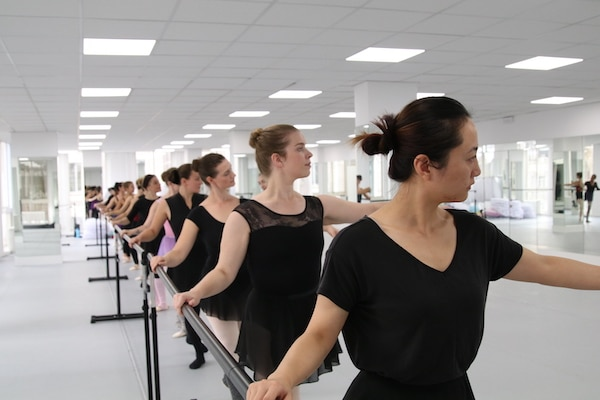 women standing at the barre doing ballet