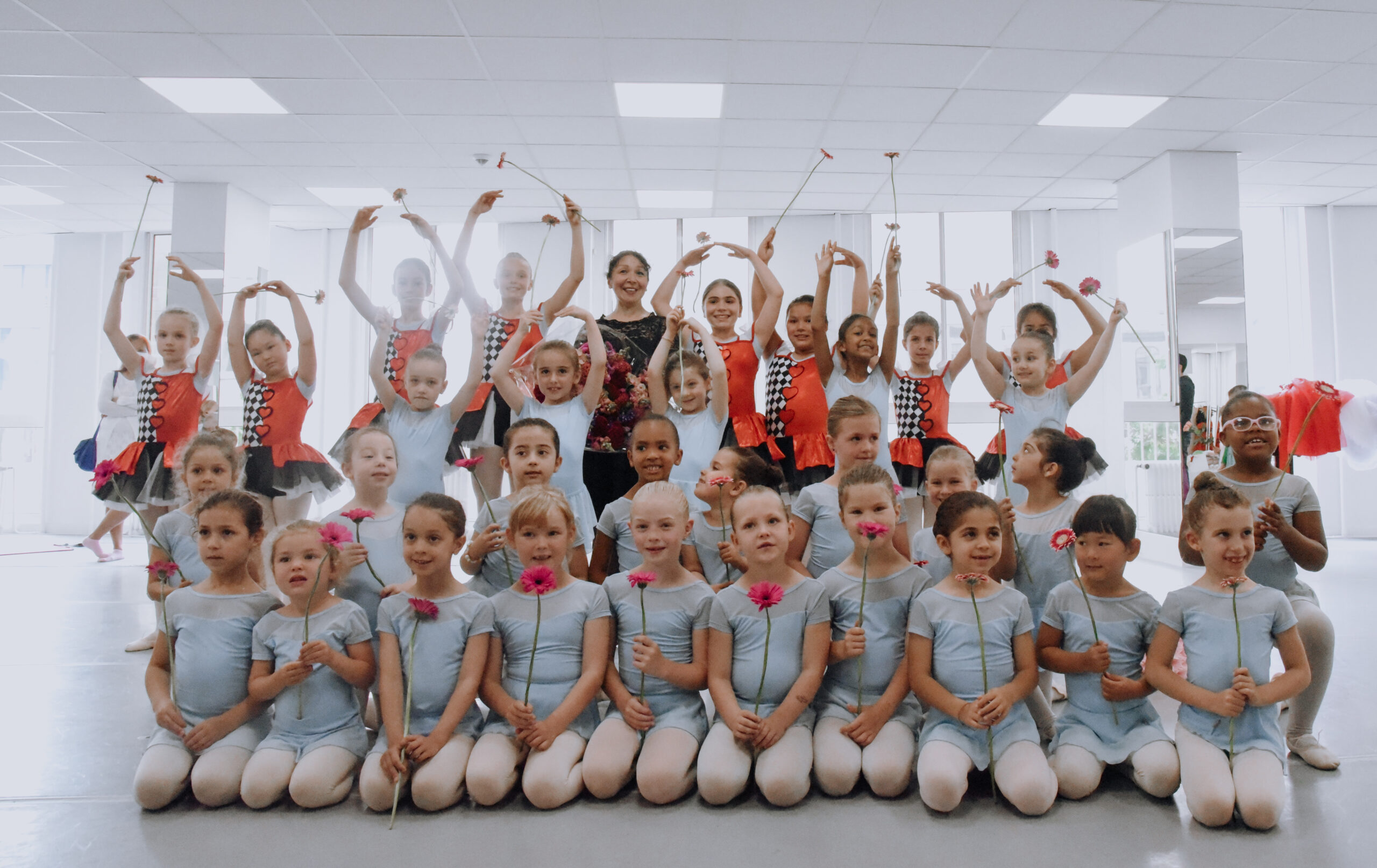 children in a ballet studio holding flowers after the show